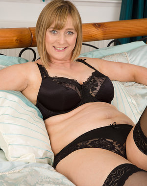 Busty mature April looks sultry in her black lingerie playing with herself in bed