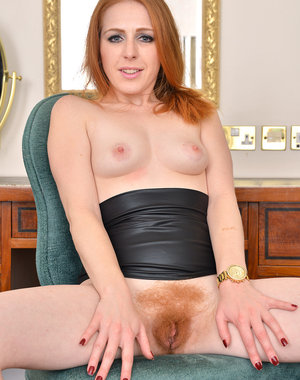 Sexy redhead babe Tia Jones slips out of her skirt and spreads her legs