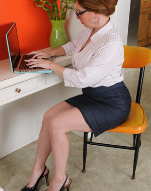 Busty secretary Kiki Daire fingers her 39 year old pussy at her desk