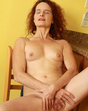 Redheaded 49 year old housewife Gloria M getting naked in the kitchen