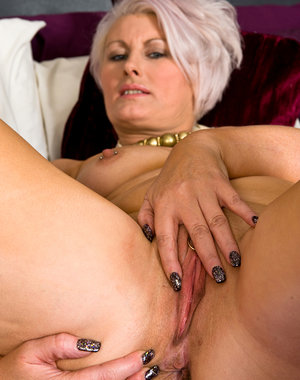 Blonde housewife Sally T exporing her mature shave pussy in bed